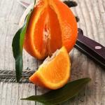 Angeschnittene Bio Clementine mit Spalt und Blatt