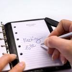 Meeting Frau schreibt Eintrag im Termin-Kalender mit Uhrzeit