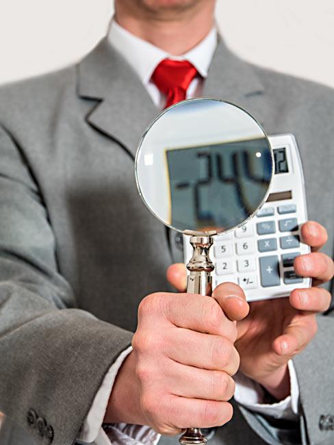 Geschäftsmann Lupe Taschenrechner - Manager mit Lupe und Taschenrechner in der Hand.