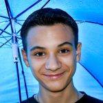 Junge unterm Regenschirm