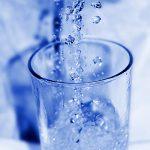 Trinkwasserglas sprudelnde Wasserperlen Tropfen