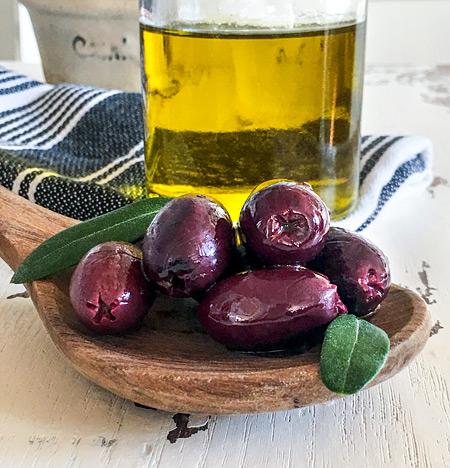 Kalamata Oliven auf Kochlöffel und Olivenöl Karaffe