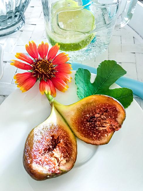 Frische aufgeschnittene Feige Ringelblume Zitronenwasser