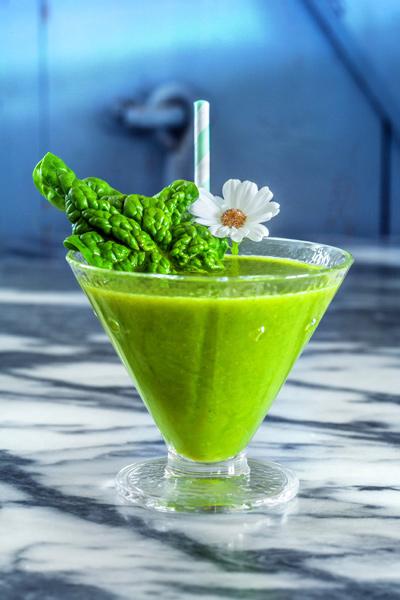 Grüner Smoothie Blattgemüse Cocktailglas Strohhalm Blüte
